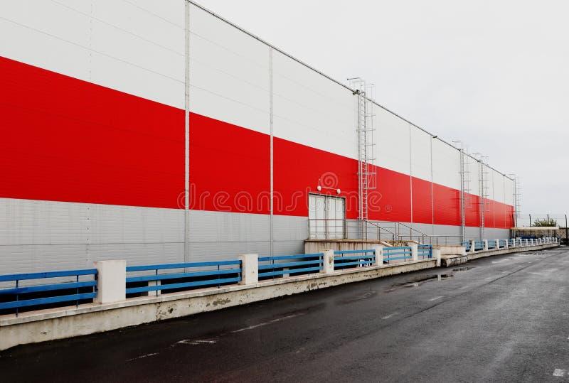工业,都市背景 红色和灰色金属墙壁和空的停车场 免版税库存图片