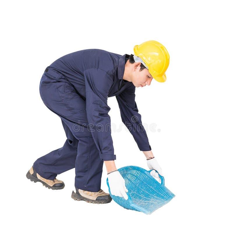 年轻工人举行煤斗或蛤壳状机件塑造了篮子 库存图片