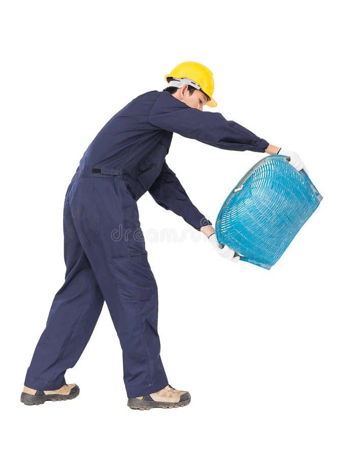 年轻工人举行煤斗或蛤壳状机件塑造了篮子 免版税图库摄影