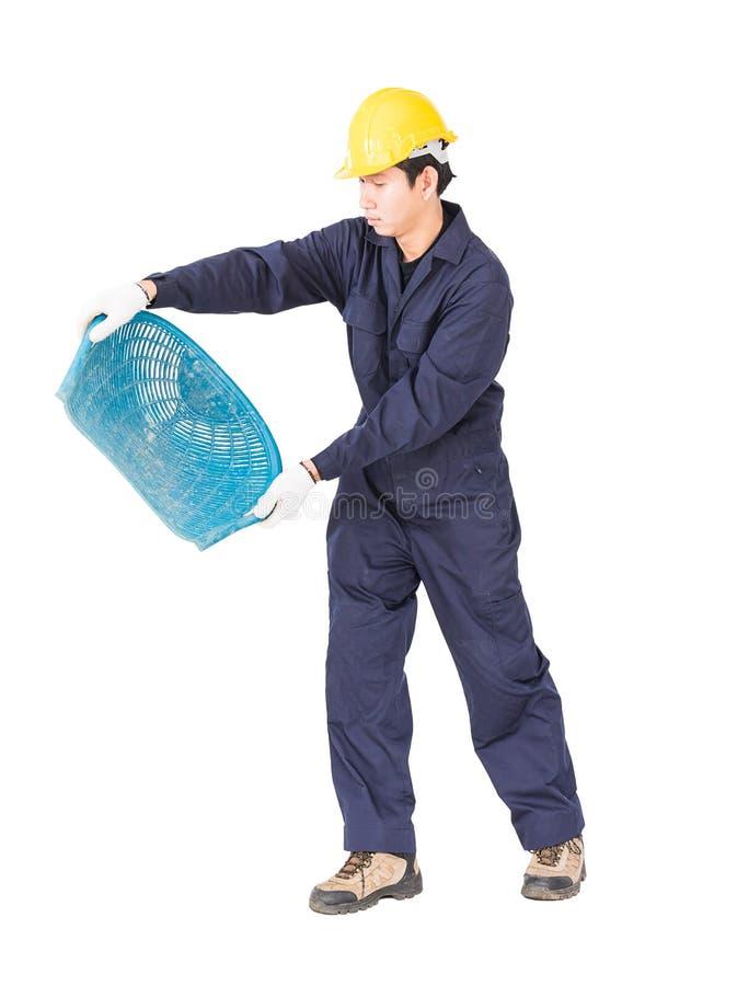 年轻工人举行煤斗或蛤壳状机件塑造了篮子 免版税库存照片