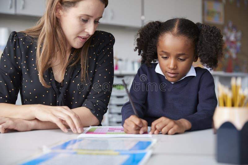 工作一在一个的年轻女性主要学校老师与观看她的女小学生赞扬在桌上在教室,关闭 免版税图库摄影