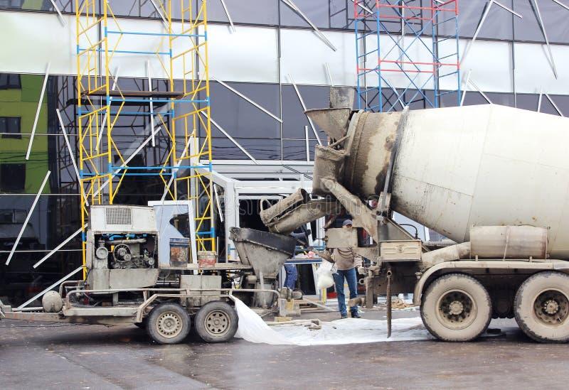 工作一起倾吐的水泥地板的混凝土泵和搅拌器在购物中心修理 库存例证