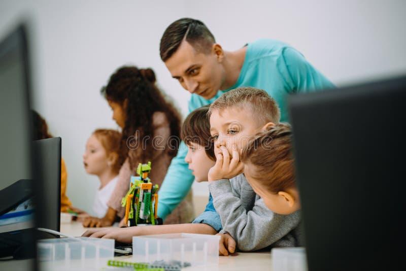 工作与他们的机器人的老师的孩子 免版税库存照片