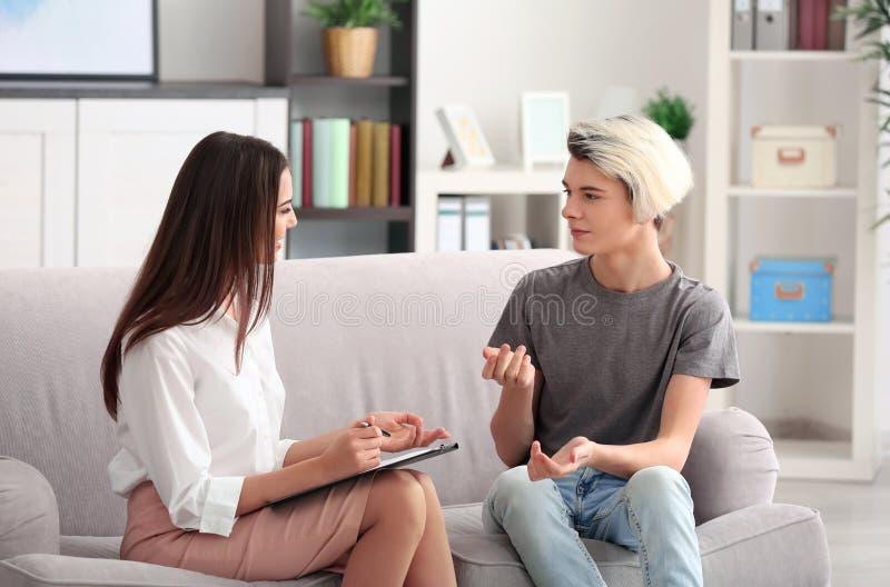 工作与十几岁的男孩的年轻女性心理学家在办公室 库存照片