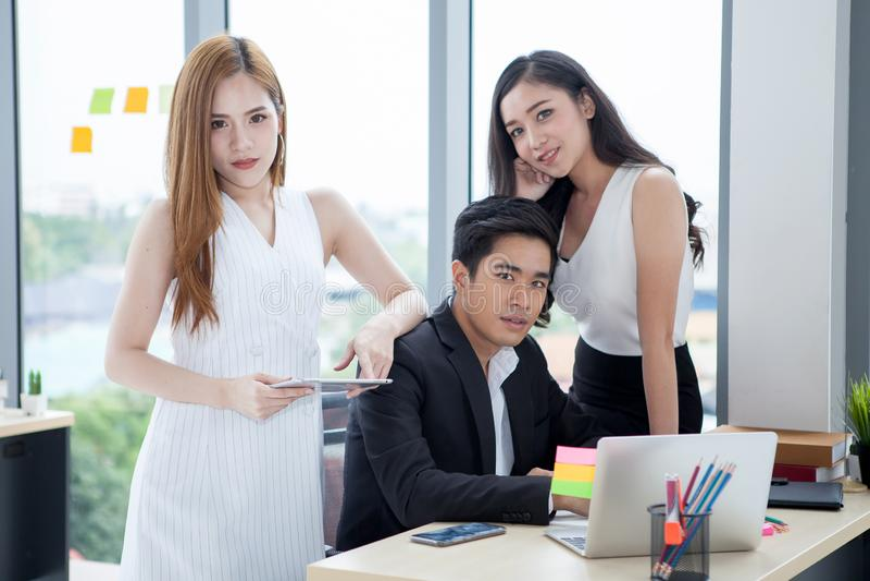 工作与在书桌上的手提电脑一起的年轻商人和两名女实业家队在办公室 上司casanova和 免版税库存照片