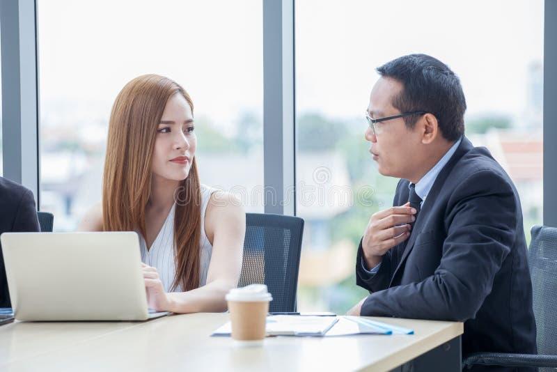 工作与在书桌上的手提电脑一起的愉快的年轻商人和女实业家队谈论信息在办公室 上司 库存照片
