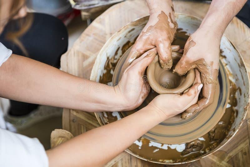 工作与女性学徒的男性陶瓷工 与在横式转盘的黏土团一起使用 免版税库存图片