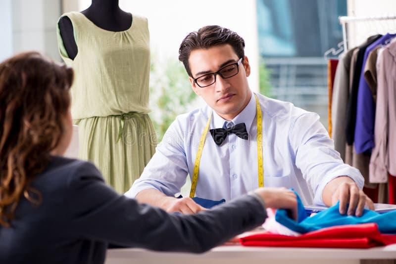 工作与女性客户的年轻人裁缝