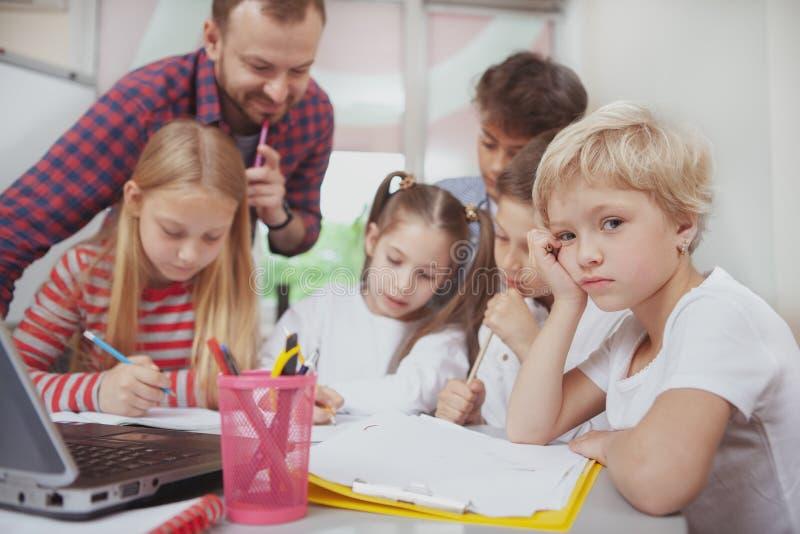 工作与孩子的男老师在幼儿园 免版税库存照片