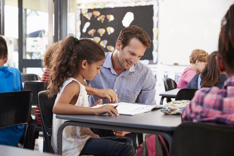 工作与年轻女小学生的老师在她的在类的书桌 库存照片