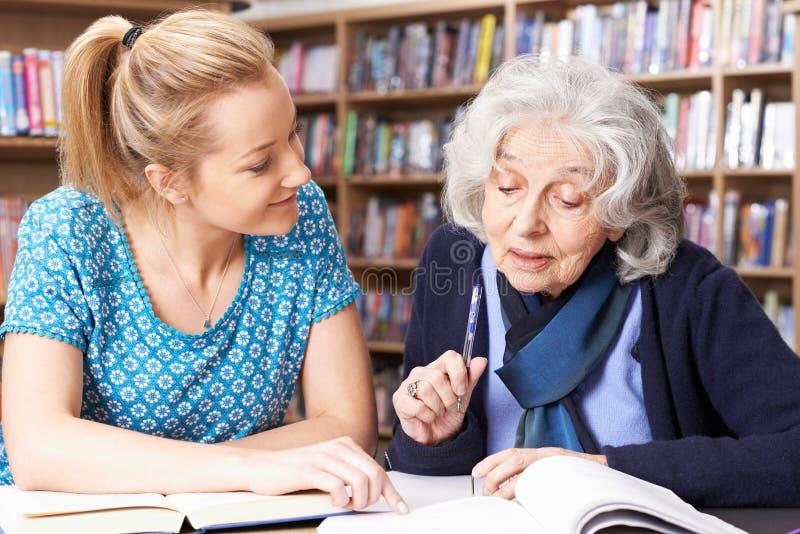 工作与老师的资深妇女在图书馆里 免版税库存照片