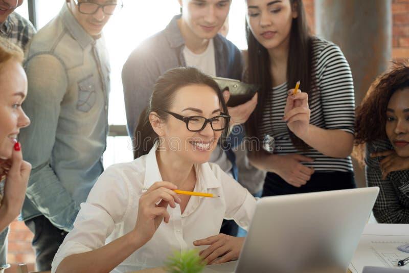工作与膝上型计算机一起的微笑的千福年的职业球队 图库摄影