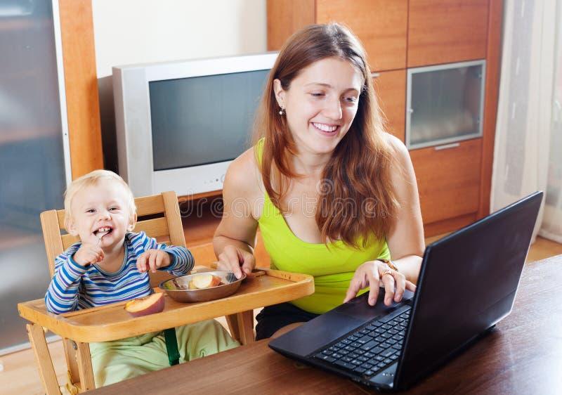 工作与膝上型计算机和婴孩的愉快的年轻母亲 库存照片