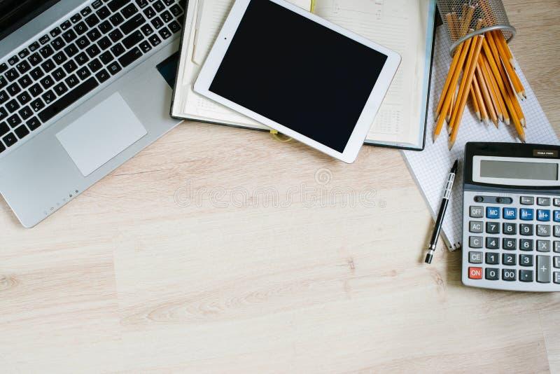 工作与膝上型计算机的办公桌桌,压片,供应和计算器 与拷贝空间的顶视图 库存图片