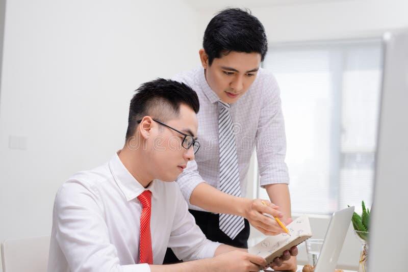 工作与计算机一起的两个商人在办公桌,指向屏幕的他们中的一个 库存图片