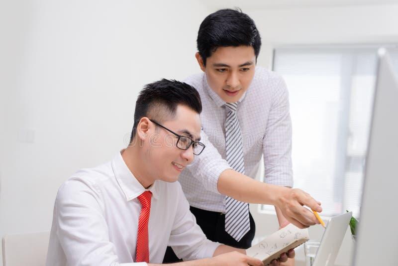 工作与计算机一起的两个商人在办公桌, o 库存照片