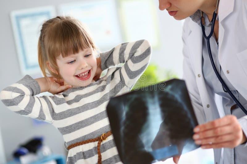 工作与逗人喜爱的女孩的女性儿科医生在她的办公室解释诊断 免版税库存照片