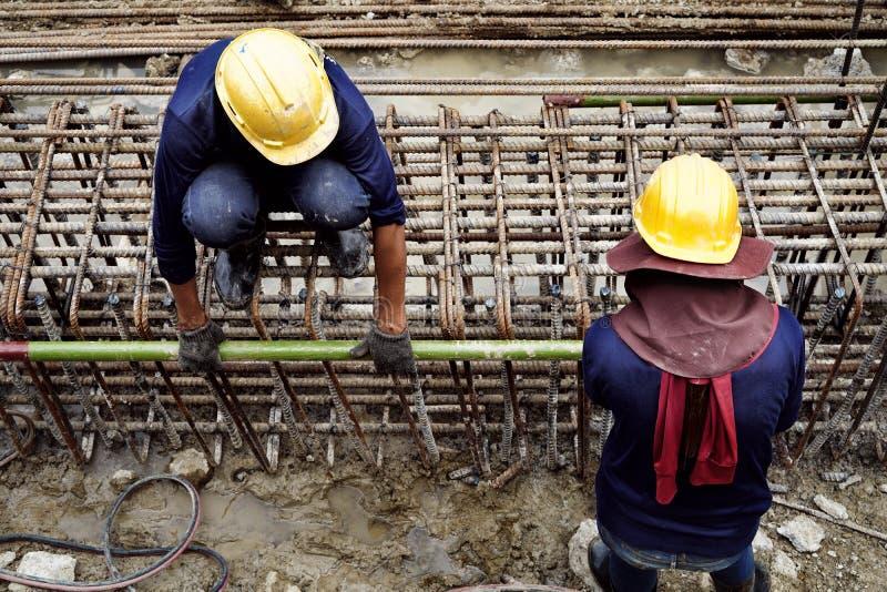 工作中戴安全帽的施工工人坐在钢筋上拿钢管脚手架管 免版税图库摄影