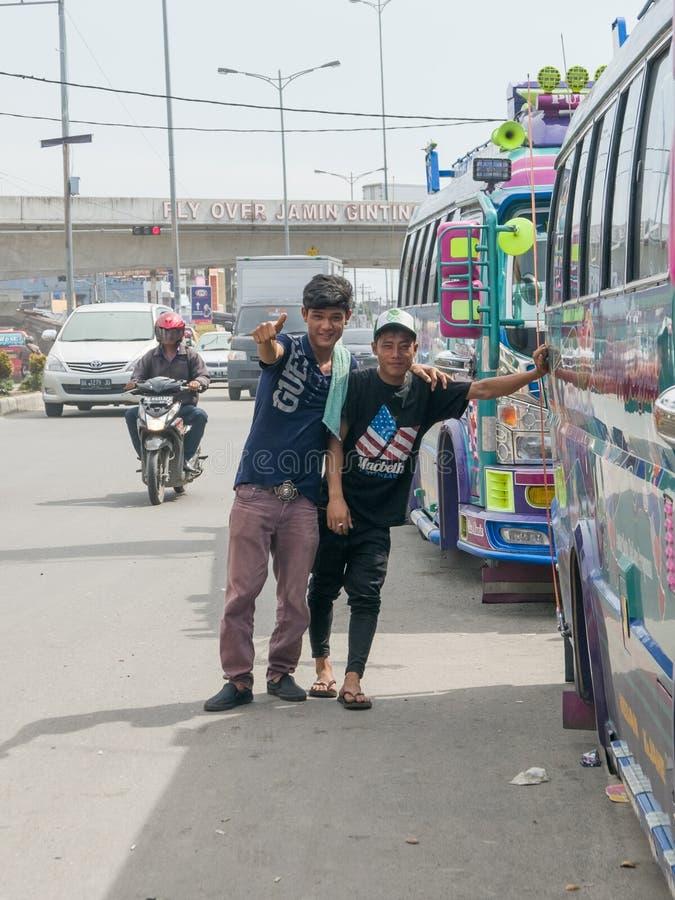 工作为运输公司的两个未认出的年轻印度尼西亚男孩在他们的微型货车旁边摆在 库存照片