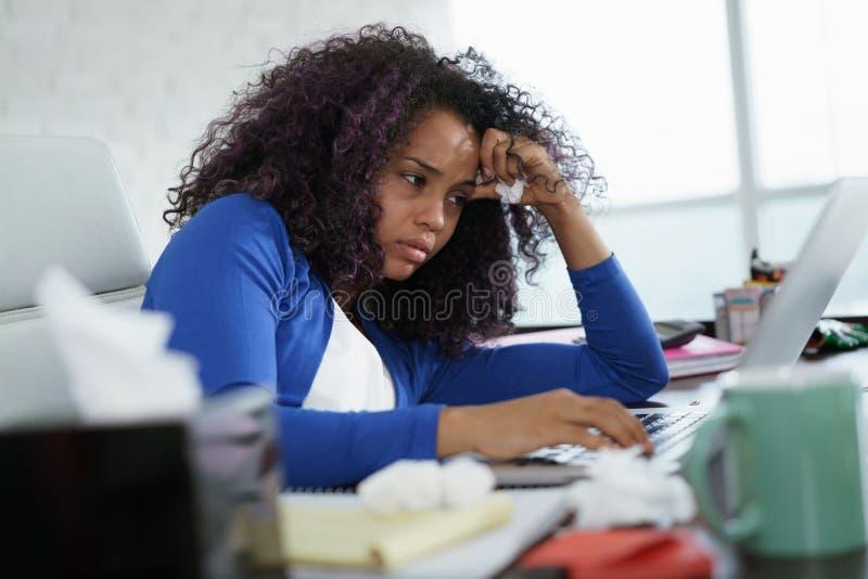 工作从家和打喷嚏为寒冷的黑人妇女 库存照片