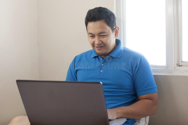 工作从家庭,愉快的微笑的表示的男性企业家网上事务看膝上型计算机 免版税库存图片