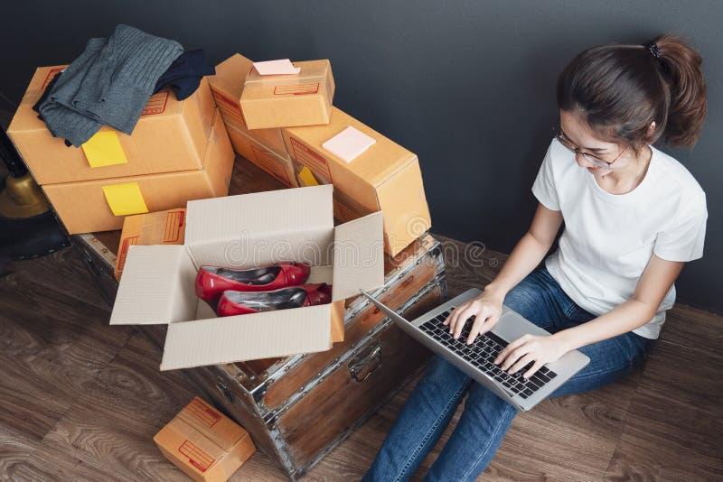 工作从家的妇女顶视图便携式计算机在与邮政小包的木地板上,卖网上想法概念 免版税库存图片