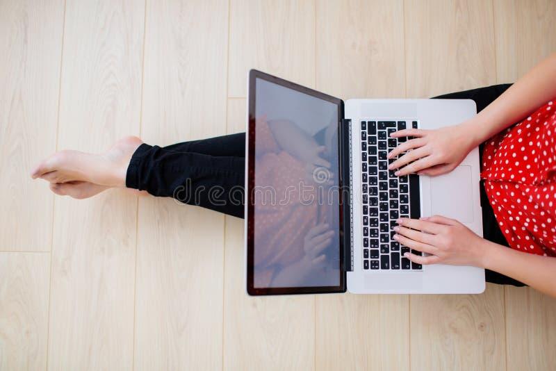 工作从有膝上型计算机的家庭办公室的年轻女人 免版税图库摄影