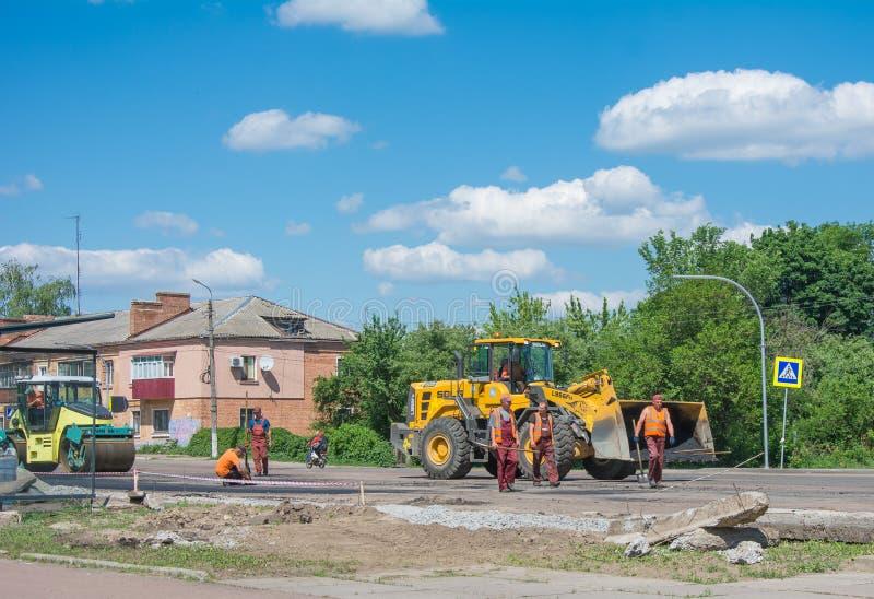工作充分修理路的旅团使用履带牵引装置沥青摊铺机新鲜的沥青路面和双重鼓路辗压紧机在 库存图片