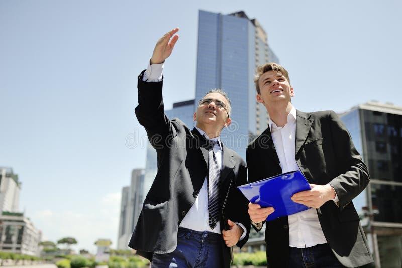 工作关于在背景办公楼的一个新的项目的两个商人 库存照片
