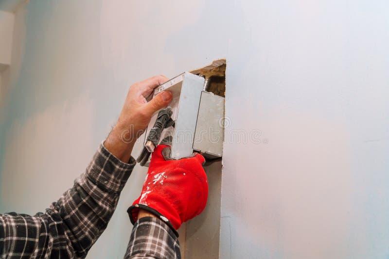 工作切口墙壁的电工缚住的看墙壁的不同的电缆 库存照片