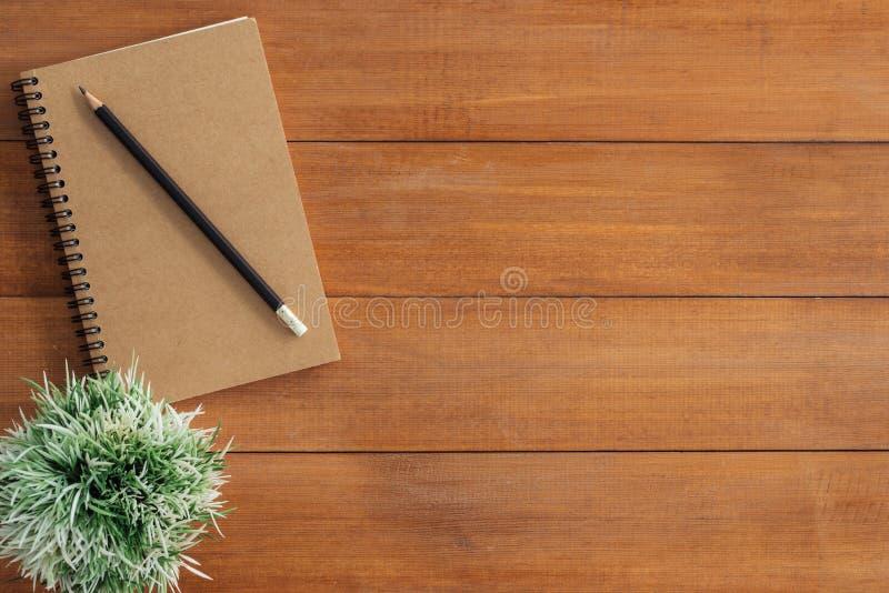 工作区书桌创造性的舱内甲板位置照片  与嘲笑的办公桌木桌背景笔记本和铅笔和植物 免版税库存图片