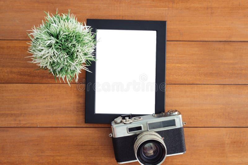 工作区书桌创造性的舱内甲板位置照片  与老照相机和海报大模型模板的办公桌木桌 免版税库存图片