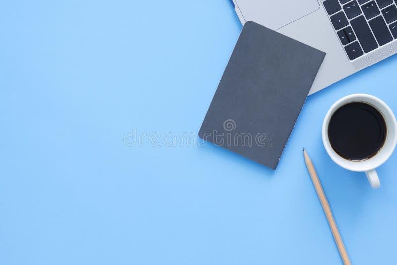 工作区书桌创造性的舱内甲板位置照片  顶视图有膝上型计算机、笔记本和咖啡杯的办公桌在蓝色颜色背景 库存图片