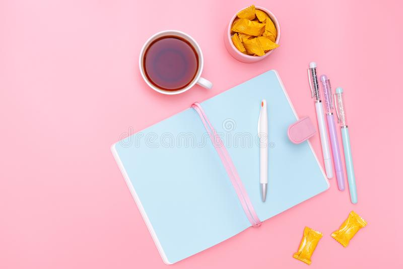 工作区书桌称呼了设计事务所供应、热的茶和糖果在桃红色淡色背景最小的样式 免版税图库摄影