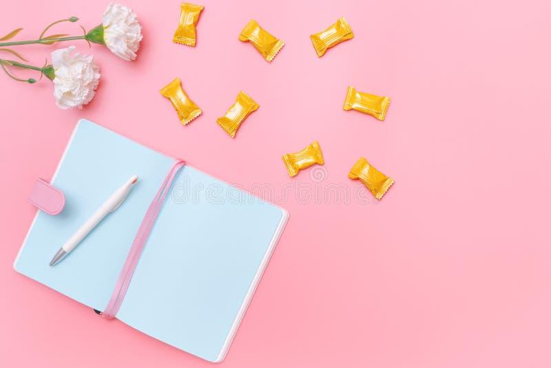 工作区书桌称呼了设计事务所供应、糖果和花在桃红色淡色背景最小的样式 免版税库存照片