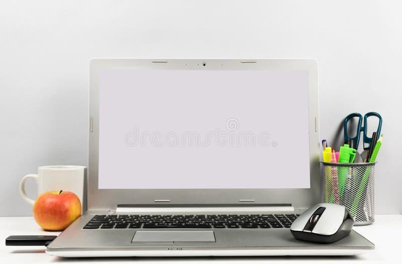工作区在与膝上型计算机、白色屏幕、咖啡,苹果、USB闪光和笔盒的桌上 图库摄影