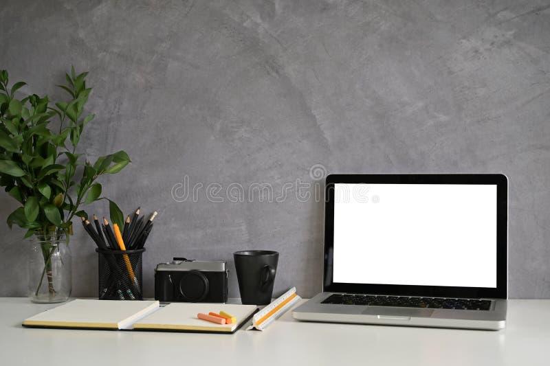 工作区桌子、笔记本电脑、相机、带阁楼墙的创意办公桌上的咖啡 免版税库存图片