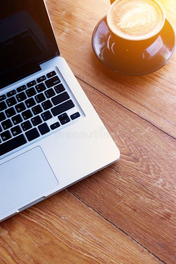 工作区概念 膝上型计算机,工作场所顶视图有膝上型计算机的在与咖啡杯的木桌上有您的文本的拷贝空间的 免版税库存照片