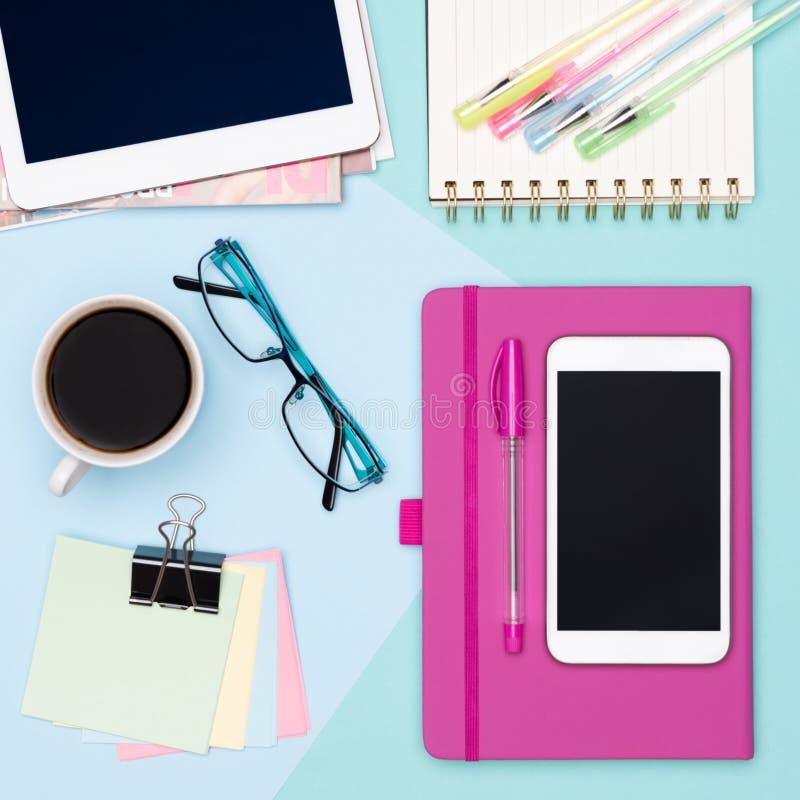 工作区顶视图照片与片剂和智能手机、咖啡、笔记薄和妇女时装杂志的 库存图片