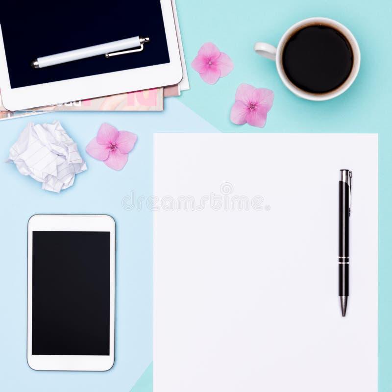 工作区顶视图照片与空白嘲笑的片剂和智能手机、咖啡杯、笔记薄和妇女时装杂志 免版税图库摄影