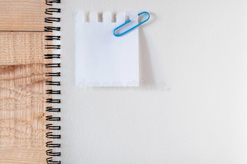 工作区,便条,与夹子纸,在木桌上的文具的剪影书 名单做它,适用于特殊场合 平的位置 免版税库存图片