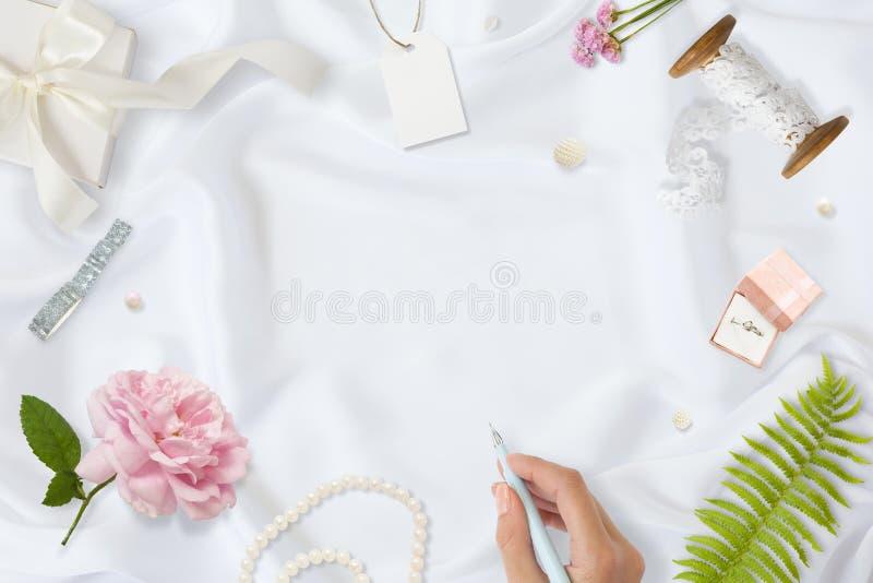 工作区 婚姻的请帖、工艺信封、桃红色和英国兰开斯特家族族徽和绿色叶子在白色缎背景 免版税库存图片