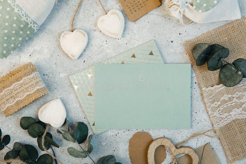 工作区 婚礼邀请卡片、工艺信封、桃红色和英国兰开斯特家族族徽和绿色叶子在白色背景 免版税库存照片