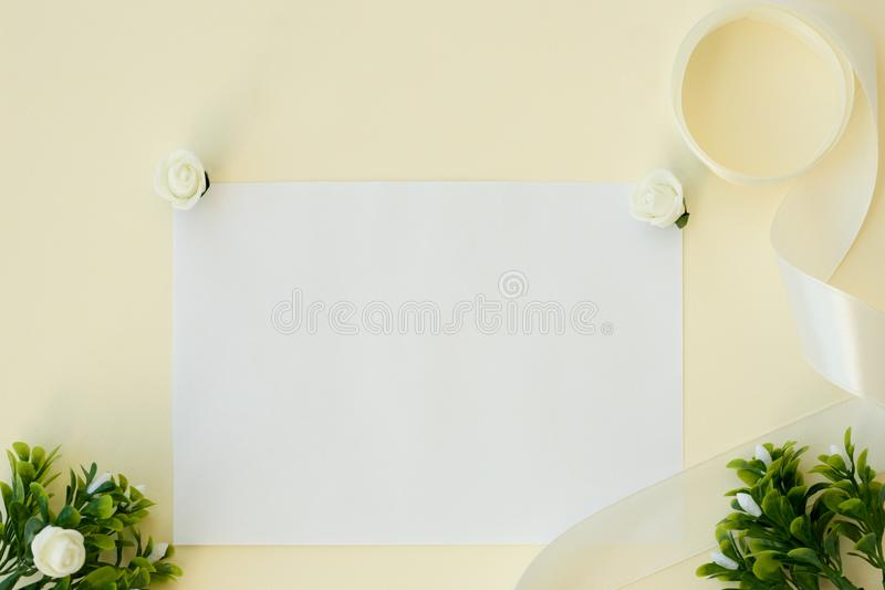 工作区 婚礼邀请卡片、缎丝带、白玫瑰和绿色叶子在米黄背景 顶上的视图 平的位置,顶面v 免版税库存图片