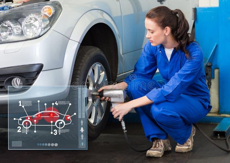 工作反对汽车修理师的女性技工在背景中连接 库存图片