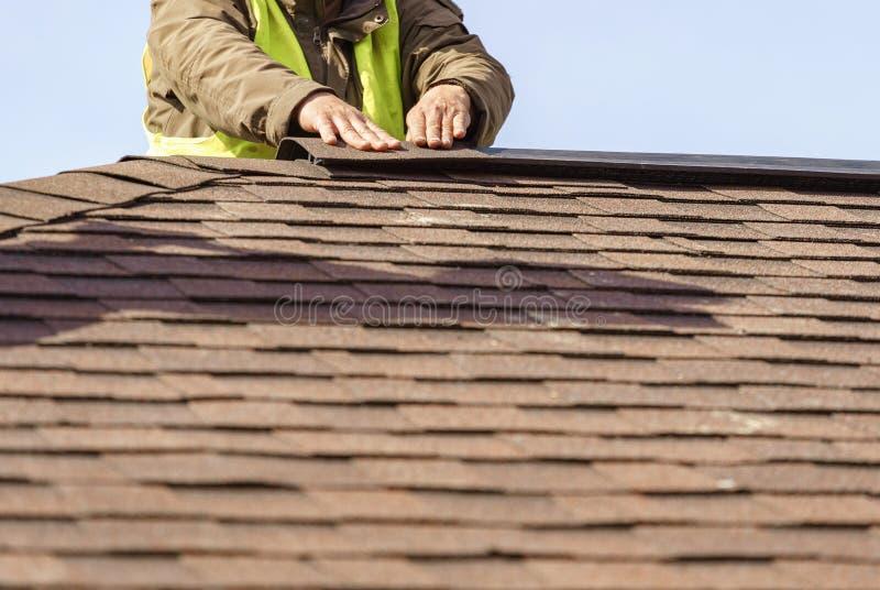 工作员在新的家安装瓦屋顶的元素建设中 免版税图库摄影