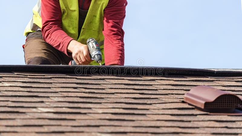 工作员在新的家安装瓦屋顶的元素建设中 库存图片