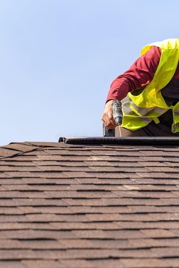 工作员在新的家安装瓦屋顶的元素建设中 图库摄影