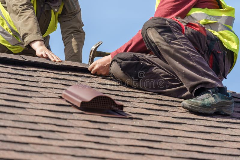 工作员在新的家安装瓦屋顶的元素建设中 库存照片