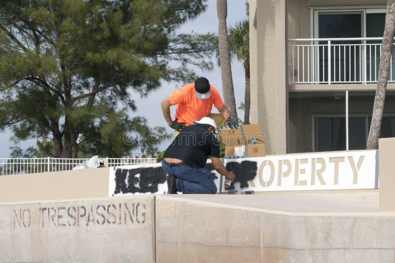 工作员绘画a让开在防波堤的标志 图库摄影